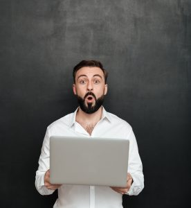 Image of excited bearded man holding silver personal computer an